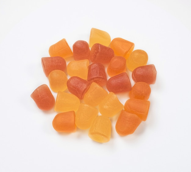 Texture en gros plan de bonbons gélifiés multivitaminés orange et jaune sur fond blanc. concept de mode de vie sain.