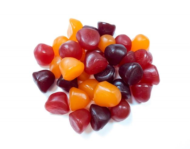 Texture en gros plan de bonbons gélifiés multivitaminés rouges, oranges et violets sur fond blanc. concept de mode de vie sain.