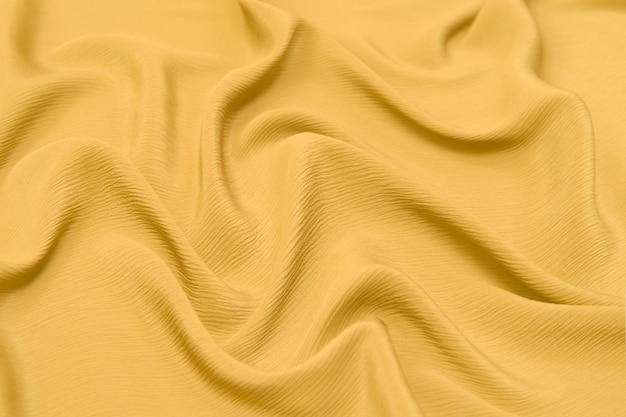 Texture en gros plan de tissu ou de tissu orange ou jaune naturel de la même couleur. texture de tissu de coton naturel, de soie ou de laine, ou de matière textile en lin. fond de toile jaune.