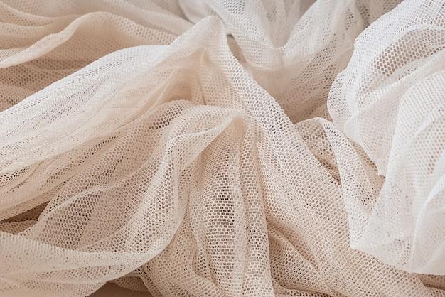 Texture en gros plan de tissu de tulle ivoire froissé, fond