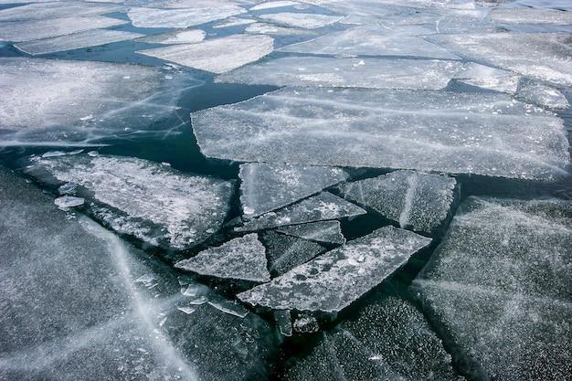 Texture d'hiver avec des morceaux de glace flottant sur l'eau
