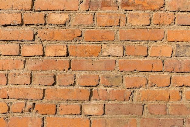 Texture inégale rugueuse vieux mur de brique rouge close up