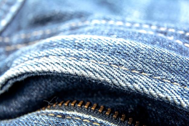Texture de jeans en denim bleu usé avec fermeture éclair / fond de texture de jeans abstrait