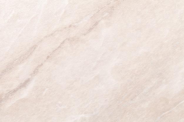 Texture de marbre beige clair avec des lignes brunes, fond macro.