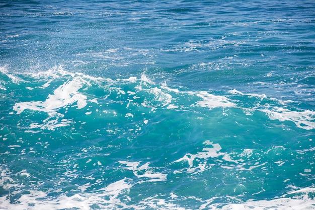 Texture de la mer bleu turquoise avec des vagues et de la mousse.