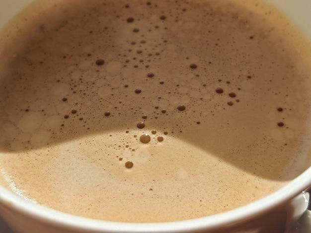 Texture de mousse de café café turc traditionnel. fermer. vue de dessus. savoureuse boisson chaude du matin. bulles de café chaud