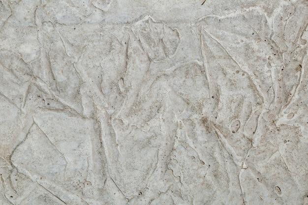 Texture de mur en béton avec une couche inégale de mastic texturé