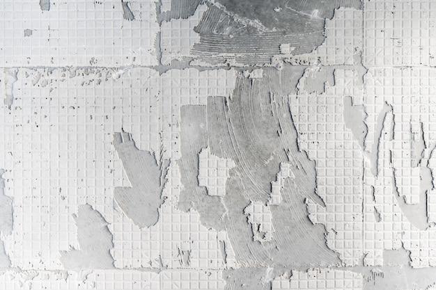 Texture de mur en béton à la surface du motif de plâtre de colle rigide après avoir retiré les carreaux avant la rénovation entreprise d'amélioration et de rénovation domiciliaire.