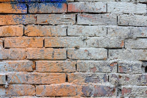 Texture de mur de brique rouge ancien peint avec des taches de mortier de ciment. fond de mur de brique abstraite