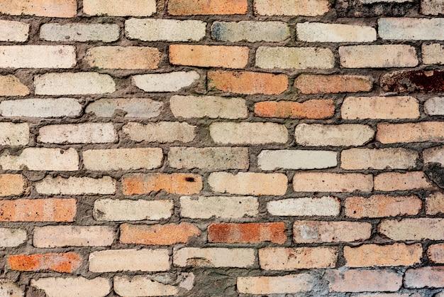 Texture d'un mur de briques avec des fissures et des rayures