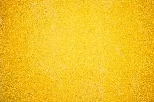 Texture de mur de ciment ou de béton jaune pour le fond