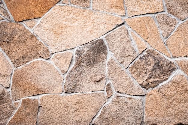 Texture de mur en pierre brune, fond grunge, modèle abstrait de mosaïque, surface de roches