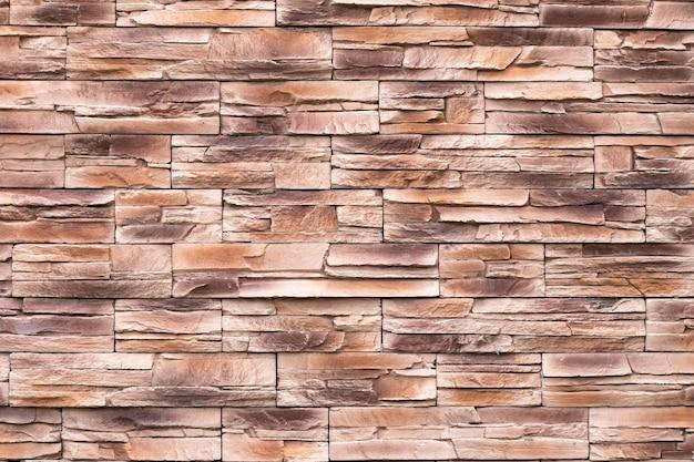 Texture de mur en pierre brune, surface inégale, fond de brique grunge, motif abstrait, surface de roches, granit rugueux. façade des bâtiments. toile de fond texturée, élément de conception. carrelage ancien. maçonnerie, maçonnerie