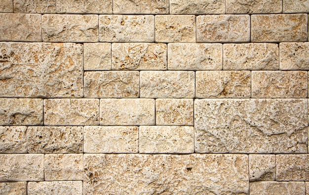Texture de mur en pierre, carreau de travertin jaune carré. élément de conception ou arrière-plan.
