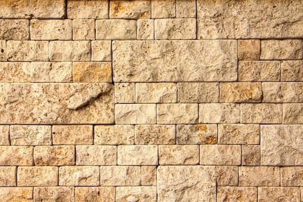 Texture de mur en pierre, carreau de travertin jaune carré.