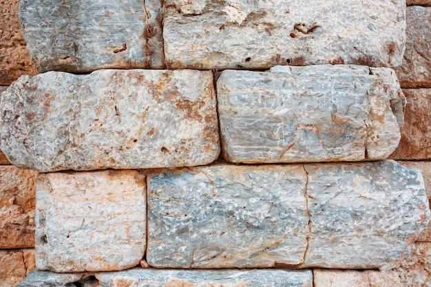 Texture d'un mur de pierre faite de gros blocs, éléments de la construction de l'antiquité antique.
