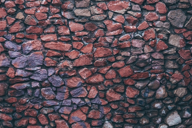 Texture de mur en pierre humide sombre colorée de granit peint inégale