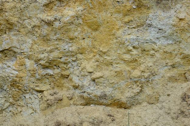 Texture d'un mur de sable solide jaune et brun dans une carrière de sable
