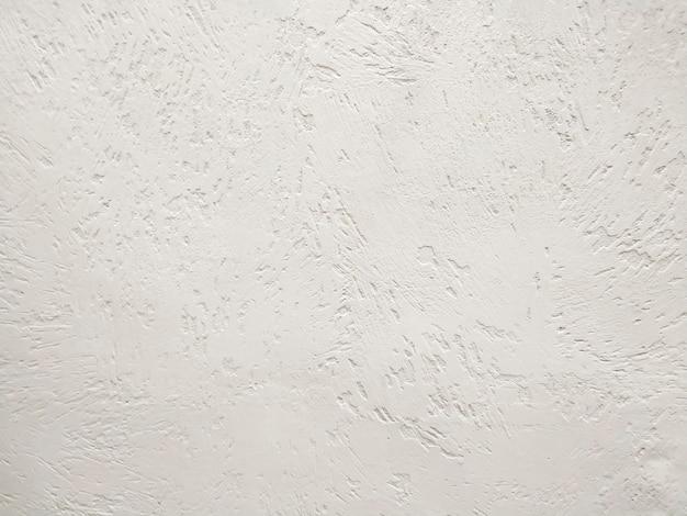 Texture de mur en stuc blanc la photographie de fond. la texture piratée à la hâte évoque une énergie de mouvement continu. conception de matériaux pour l'extérieur et l'intérieur du bâtiment