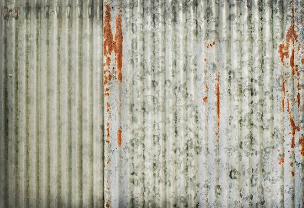 Texture de mur en zinc ancien, rouillée sur des panneaux métalliques galvanisés.