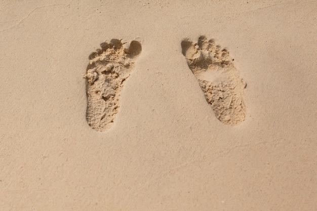Texture naturelle et arrière-plan. empreintes de pas dans le sable jaune sur la plage