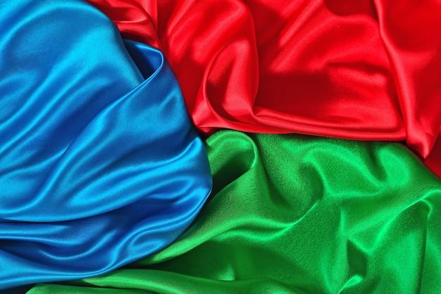 Texture naturelle de tissu de satin bleu, rouge et vert