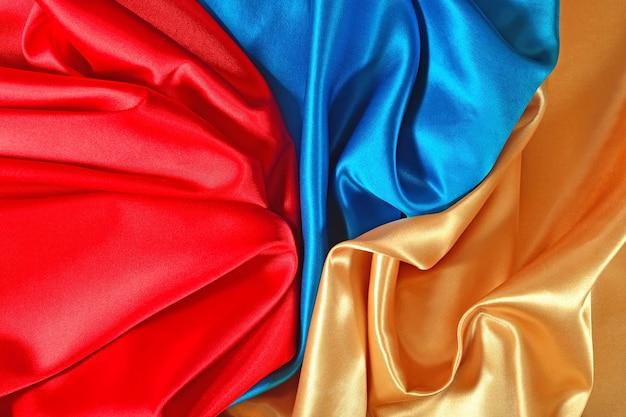 Texture naturelle de tissu de satin doré, bleu et rouge