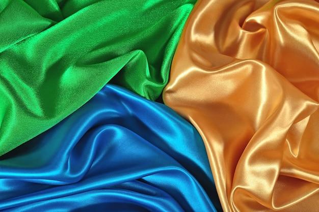 Texture naturelle de tissu de satin doré, bleu et vert