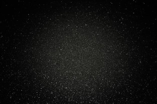 Texture noire avec micro-relief et paillettes. texture de paillettes noires avec centre lumineux