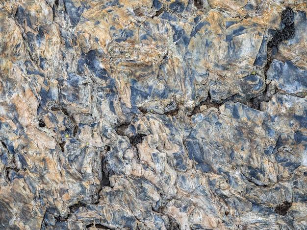 Texture ondulée de la pierre. texture détaillée multicolore d'une pente de montagne rocheuse. roche géologique.
