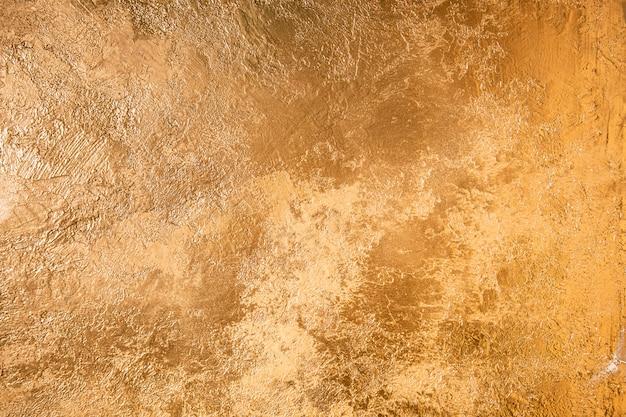 Texture or abstraite. mur coloré avec du plâtre doré.