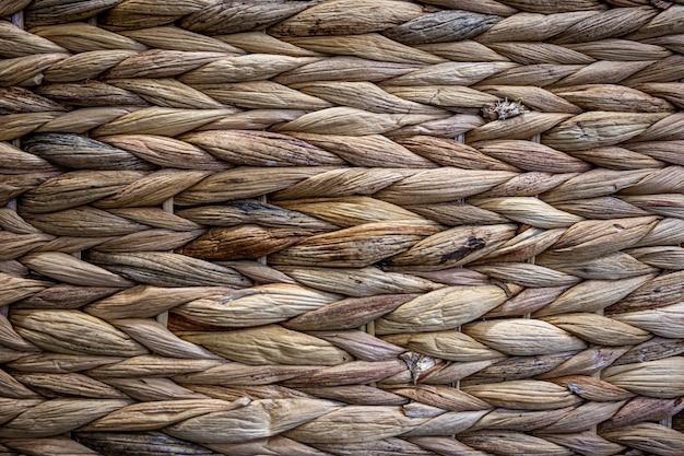Texture de paille beige tissée, fond de tresses du gros plan de la tige de la plante.