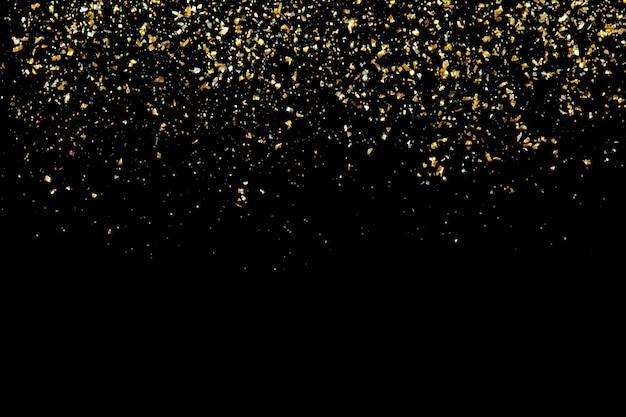 Texture de paillettes dorées sur résumé noir