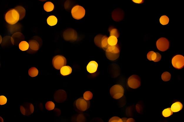 Texture de paillettes d'or abstraite floue, lumières de noël défocalisés sur fond noir