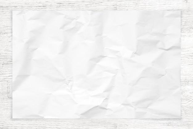 Texture de papier froissé sur fond de bois blanc.