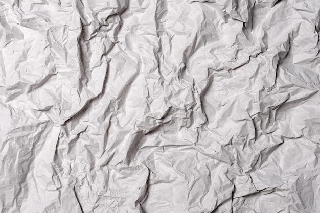 Texture de papier gris froissé. fond de papier froissé avec des fissures et des plis.