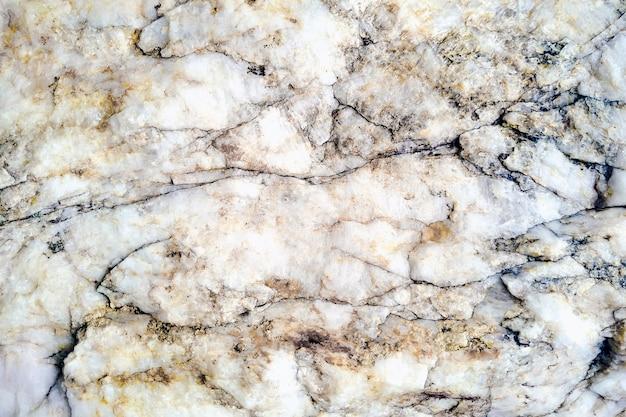 Texture de pierre blanche brute avec veiné noir et marron.
