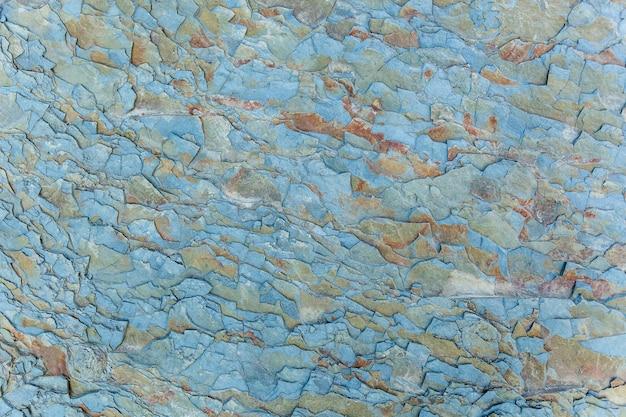 La texture de la pierre est bleue avec des taches rouges