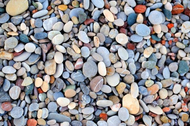 Texture de pierres de galets colorés par le fond de la plage