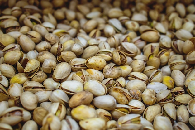 Texture pistache. des noisettes. pistaches fraîches vertes comme texture. pistaches salées grillées photo de studio de nourriture saine et délicieuse.