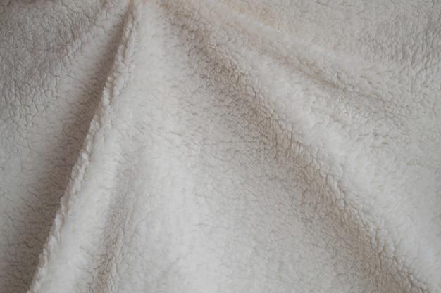 Texture d'un plaid doux. couverture chaude froissée blanche. tissu pour fond ou papier peint.
