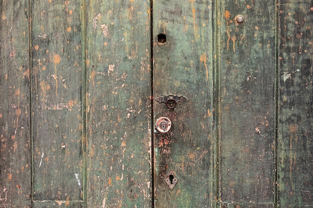 Texture de porte en bois ancienne avec des détails métalliques.