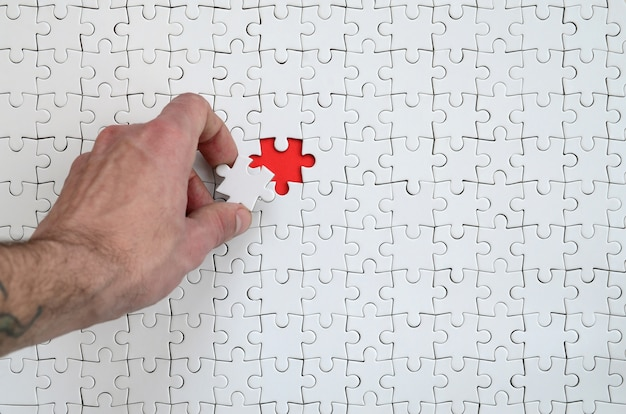 La texture d'un puzzle blanc à l'état assemblé avec un élément manquant que la main masculine met en jeu