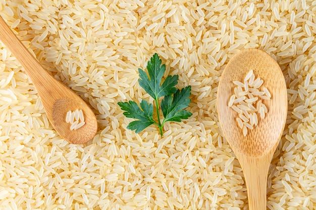 Texture de riz long jaune doré sec avec des cuillères en bois et du persil vert frais