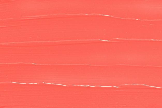Texture de rouge à lèvres corail, maquillage taché.