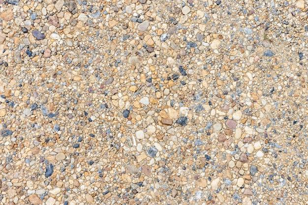 Texture de sable ou de galets colorée. texture transparente sur le sol.