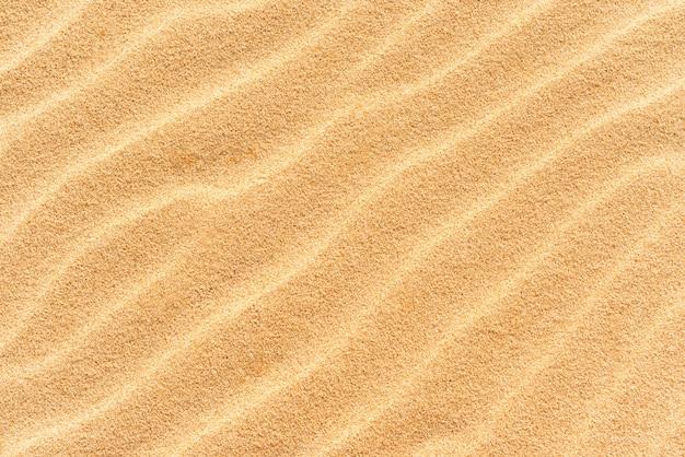 Texture de sable sur la plage avec des vagues comme fond tropical naturel