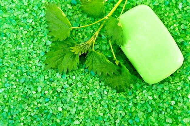 La texture des sels de bain verts avec une barre de savon vert et un brin d'ortie