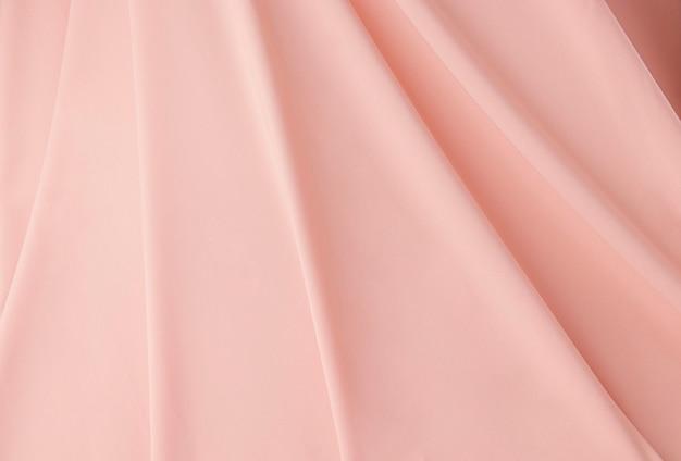 Texture de soie rose réunie en arrière-plan de plis