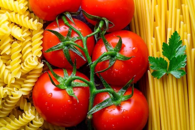 Texture de spaghetti non cuit, fusilli, persil et tomates fraîches. ingrédients pour la cuisson des pâtes italiennes